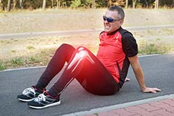 Jogger sitting on pavement in pain from runners knee.