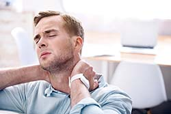 Man with neck pain holding his neck.