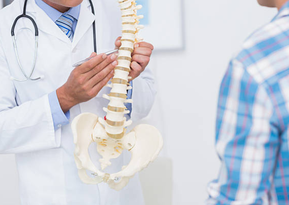 Chiropractor educating patient with spine model